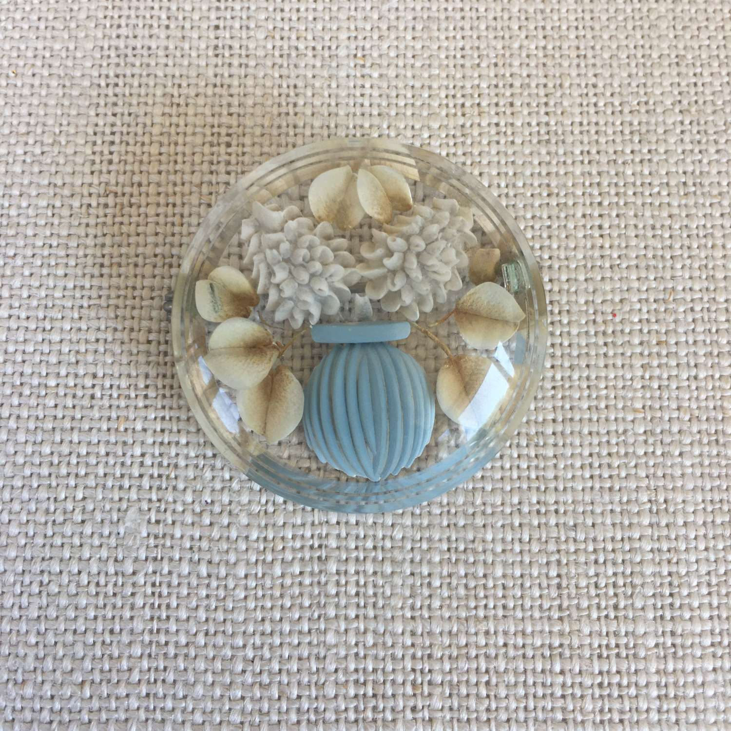 Vintage round lucite brooch with blue vase and cream flowers