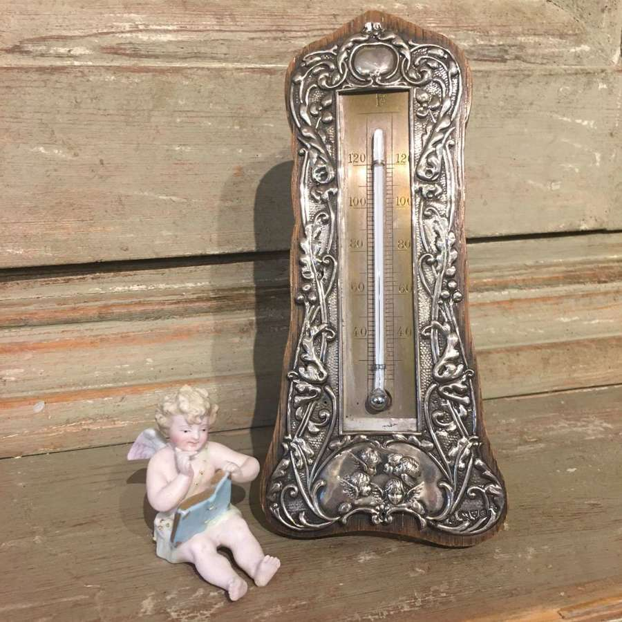 An antique silver thermometer d 1904 with cherub design